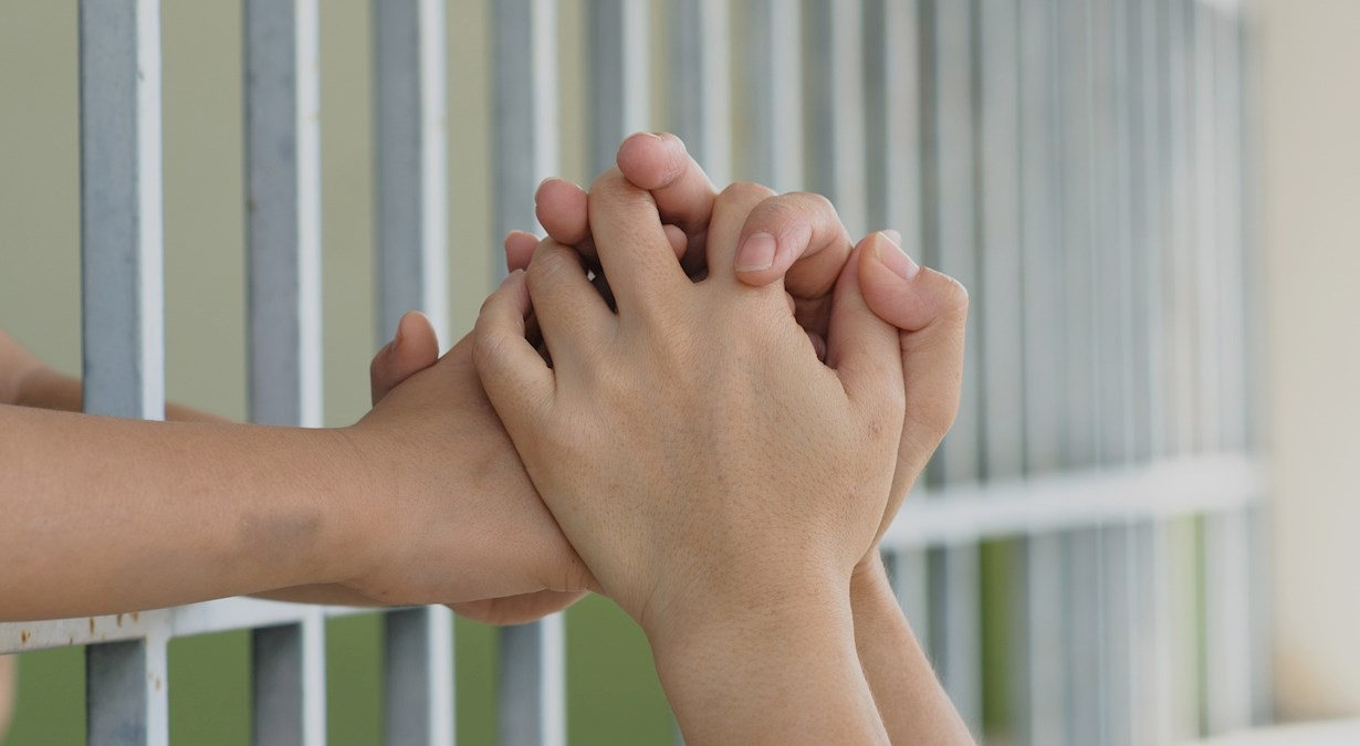 Close-up of hands being held through prison gate