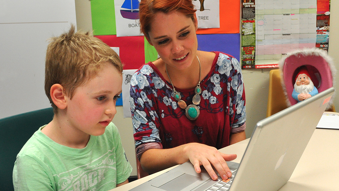 Woman with a child looking at a laptop
