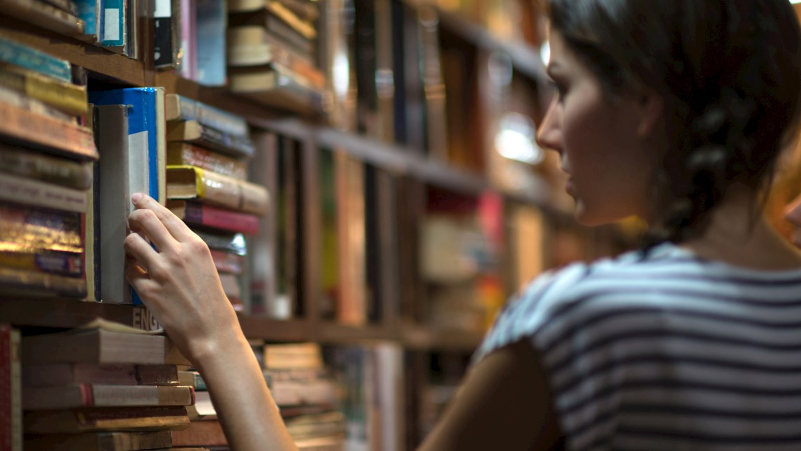 Young woman selecting a book from a shelf