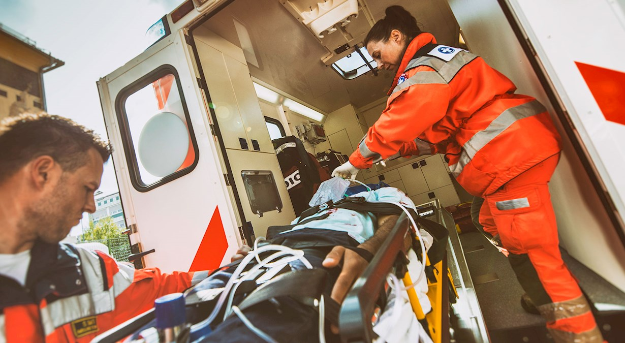 image of paramedics loading a patient into an ambulance