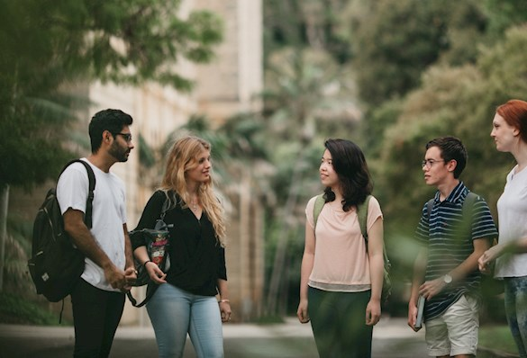 Students chatting at a university campus. Skin tone ranges from pale to dark brown