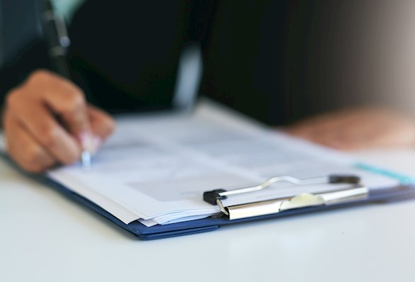 Person at a desk, holding a pen to fill in a form