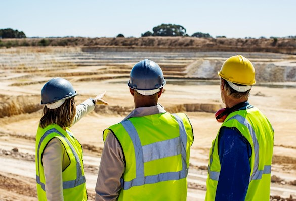 Backs of three people wearing hi-vis tops and helmets, surveying a mining site