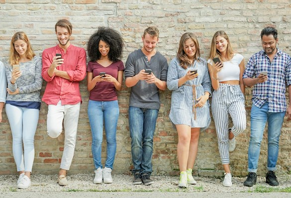Group of young people leaning on a wall and looking at their mobile phones