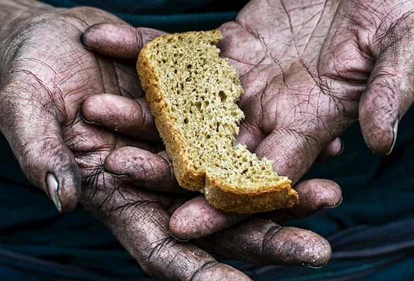 Soiled hands holding a small portion of bread