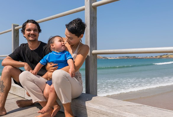 Indigenous man and woman with toddler sitting on pier