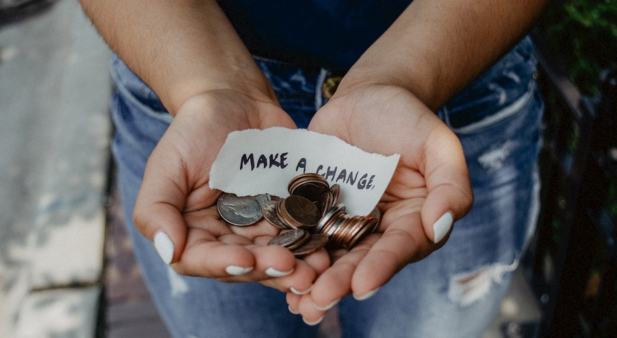 Person showing both hands with 'make a change' note and coins