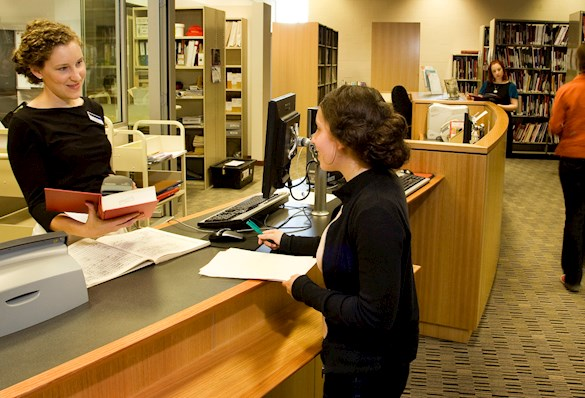 Interior view of Wigmore Music Library with staff member helping a visitor