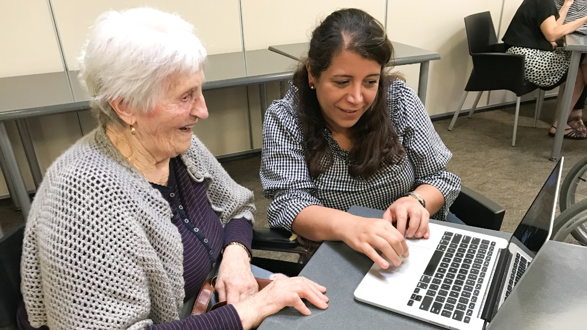 Two women, one elderly, sitting together at table looking at laptop
