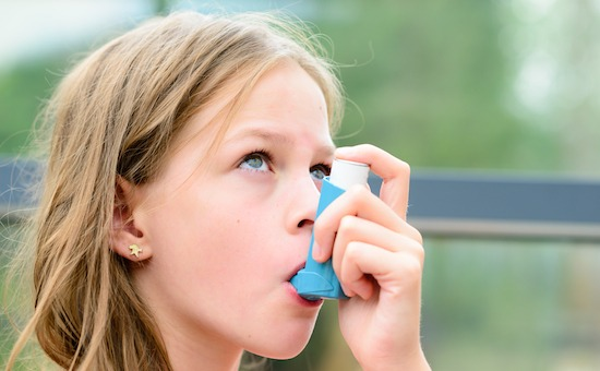 Child using Salbutamol inhaler