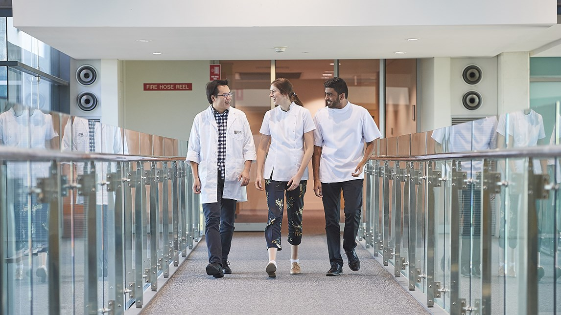 3 students walking down a hallway