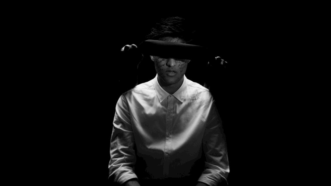 Still image from a video with a blindfolded person in black and white
