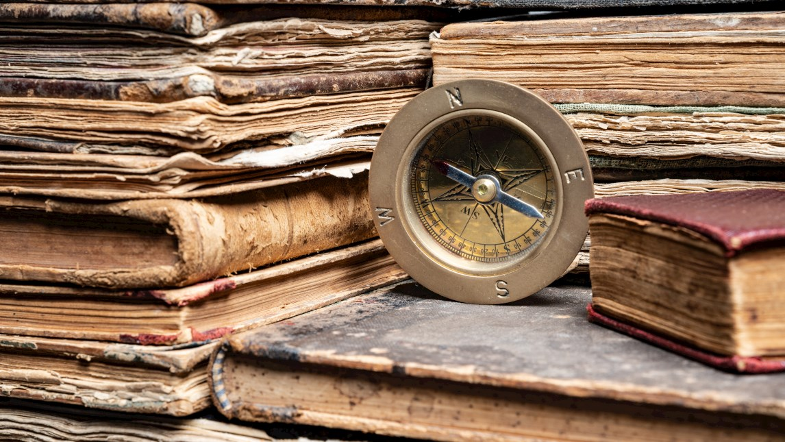 compass on stack of antique hard cover books