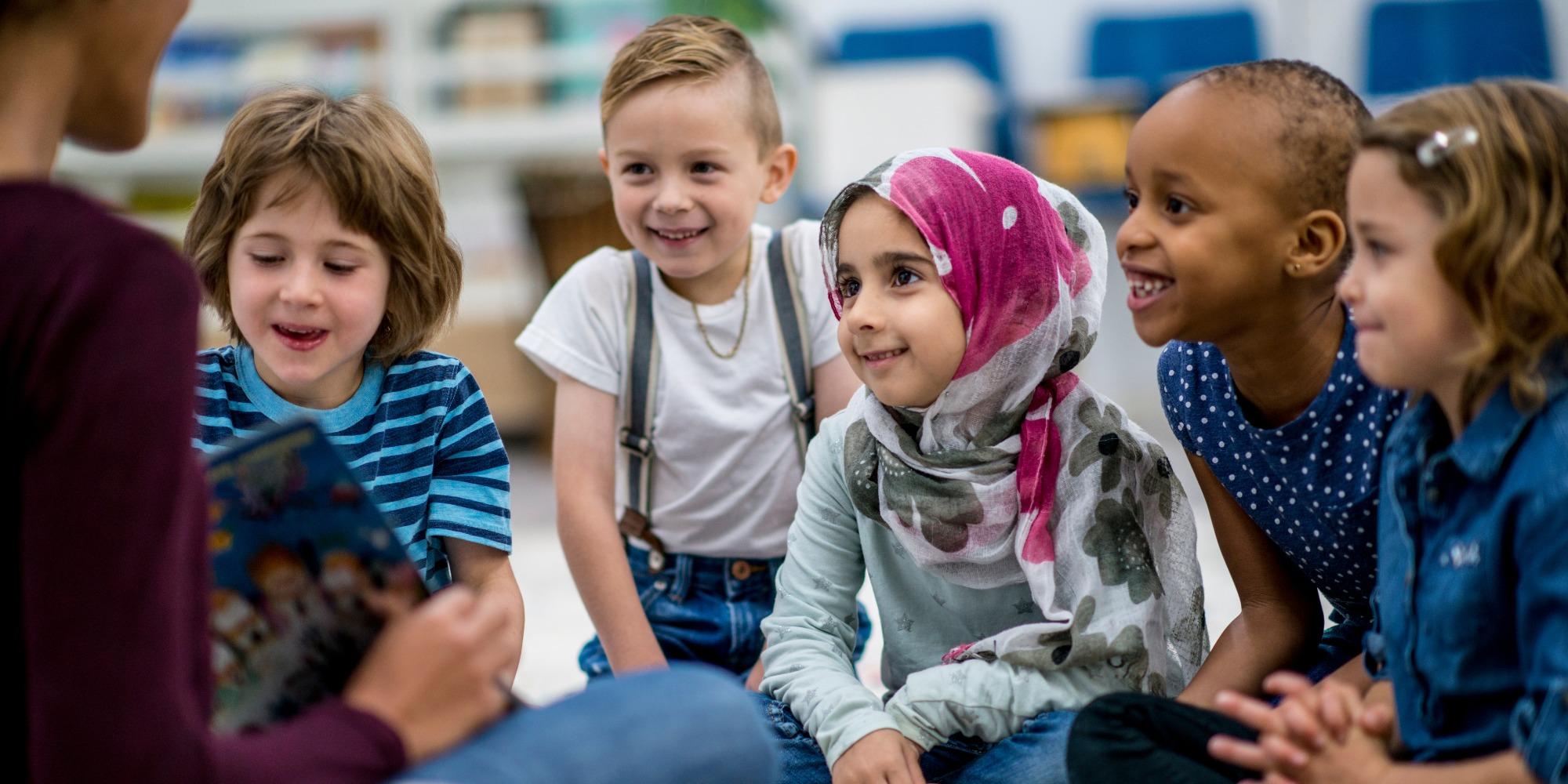 children listen to their teacher read a book to them