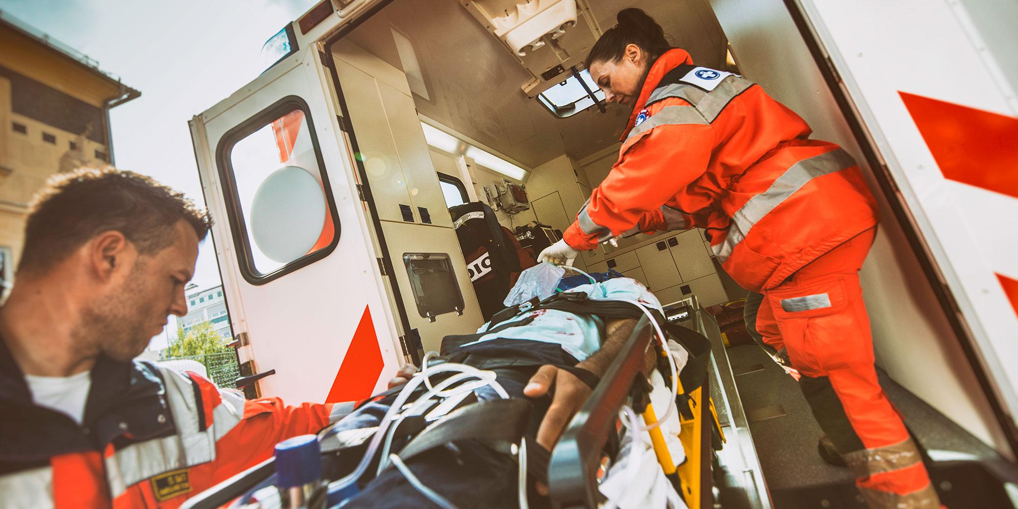image of paramedics loading a patient into an ambulance