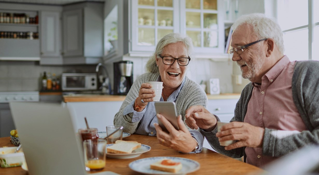 Two old people looking at a smartphone