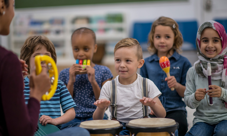 Kindergarten aged children playing musical instruments