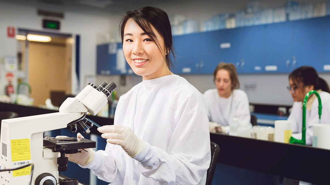 Woman in doctors coat  in lab at microscope