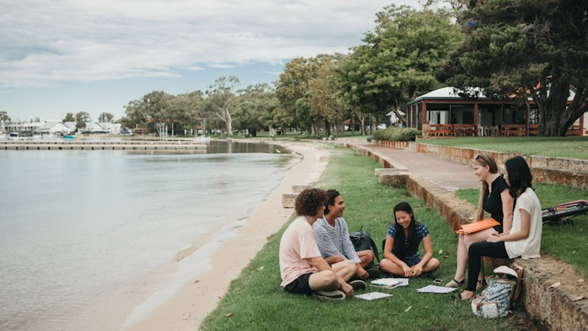 Group of UWA students sitting on Swan River foreshore