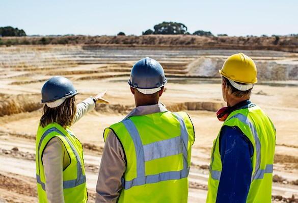 3 people standing in a mining construction quarry