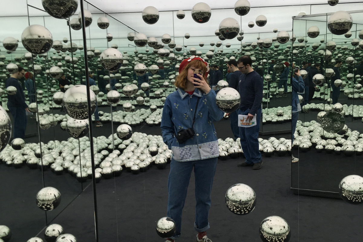 UWA Fine Arts student Zoe taking a selfie at a gallery, surrounded by silver balls and mirrors