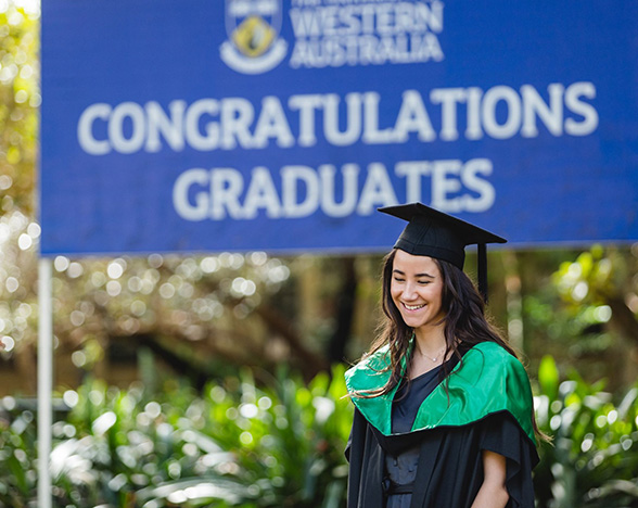 A smiling graduate outdoors in front of a sign which reads 'Congratulations graduates'