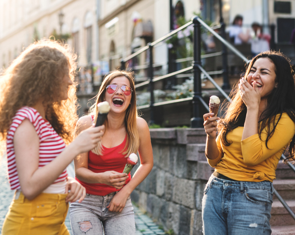 Three young women eating ice cream and laughing