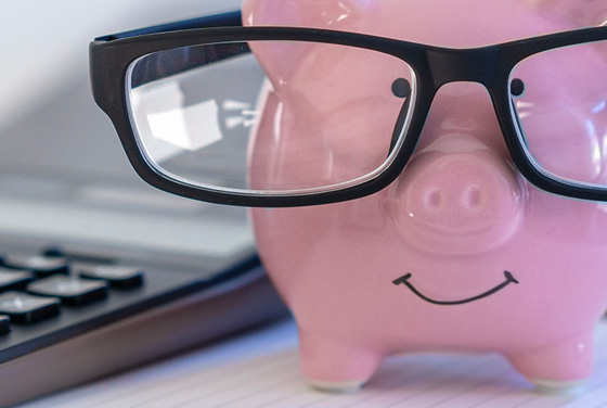 Plastic piggy bank wearing spectacles