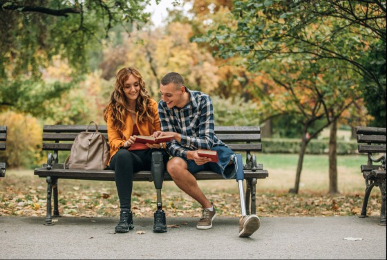 Two people with one prosthetic leg sitting on a park bench