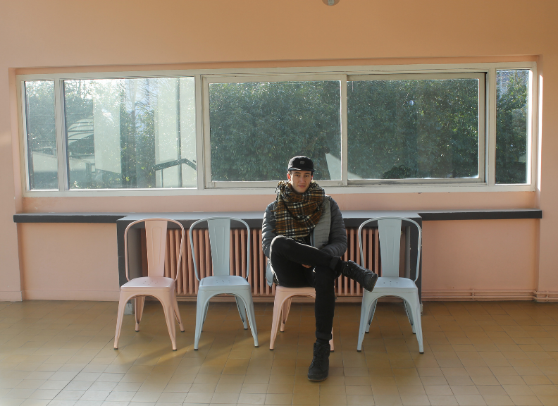 Architecture student Nic sitting on a chair at Villa Savoye, Paris