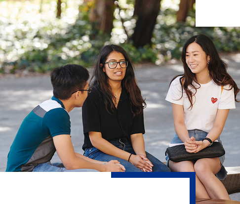 Three students sitting and talking outside
