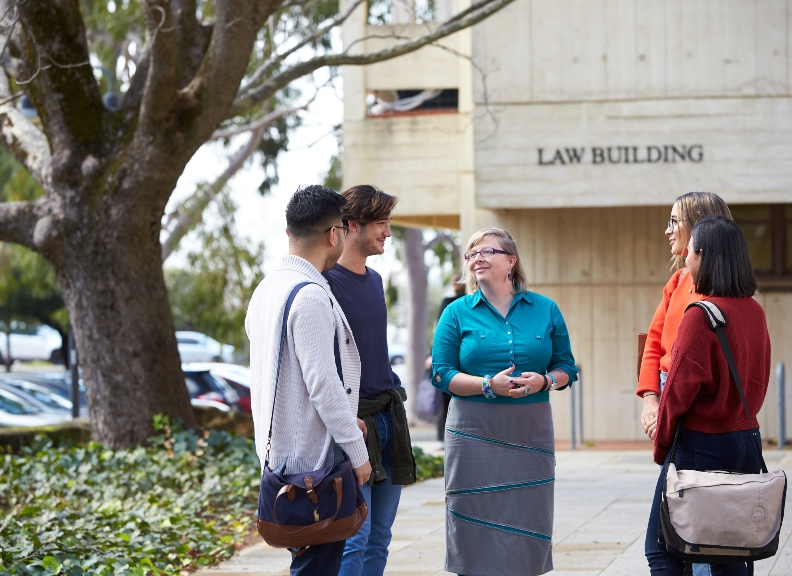 Students speaking with academic in front of the UWA Law building