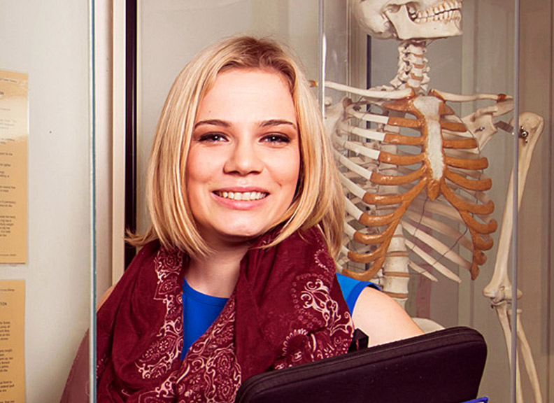 student in front of skeleton