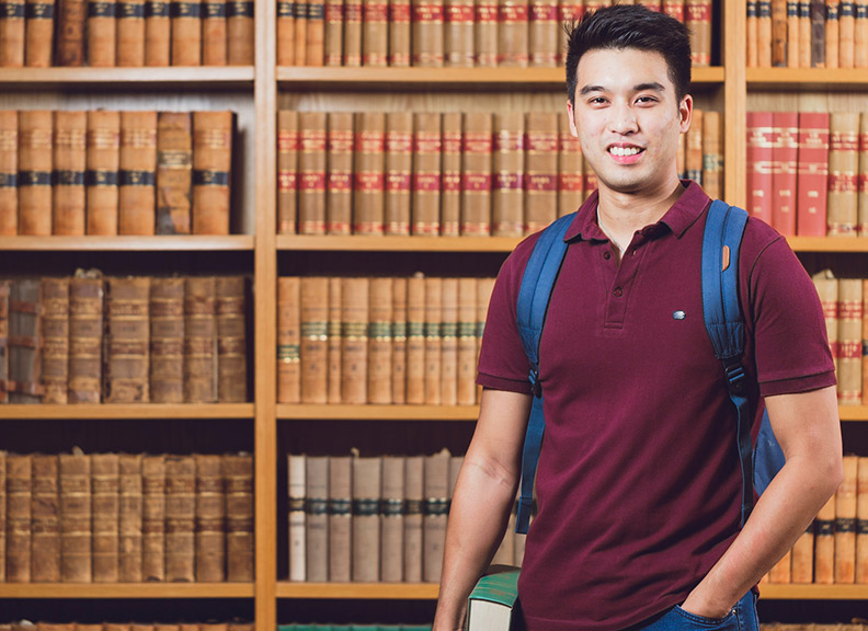 student in front of bookcase