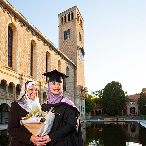 Graduate outcomes - university graduate in robe with her mother outside Winthrop Hall